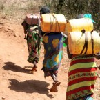 Mujeres cargando agua a la espalda